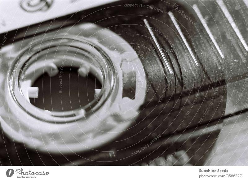 Makro-Nahaufnahme eines alten Plastikkassettenbandes in Schwarz-Weiß Musik Rolle SCHWARZ-WEIß schwarz-weiß schwarz auf weiß altmodisch veraltet Oldschool 80s