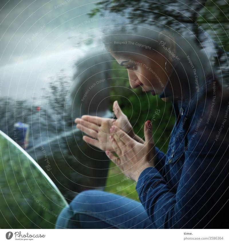 Estila frau beobachten spiegel soiegelung reflexion hände hände reiben baum jeans jacke aufmerksam ohrring profil glasscheibe