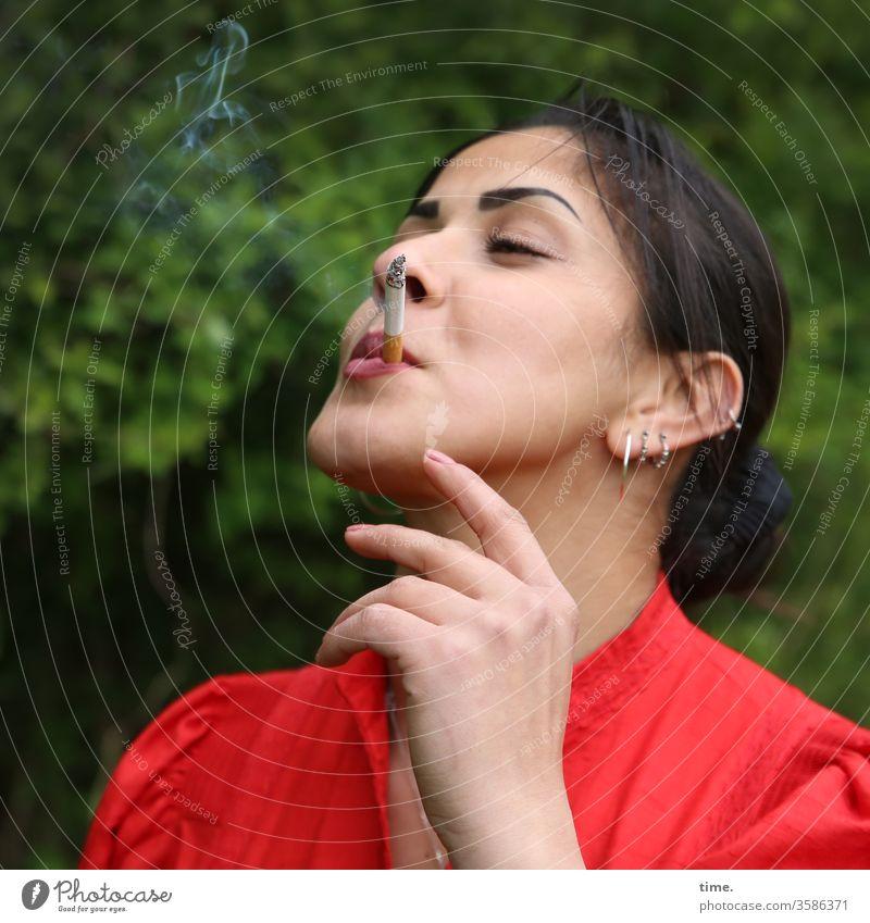 Estila frau weiblich rot rauchen selbstbewusst natur schmuck draußen dunkelhaarig langhaarig zopf genießen genuss zigarette hand geschlossene augen fröhlich