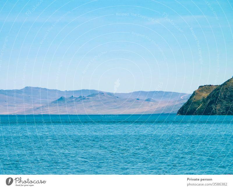 Blaues Meer, wolkenloser Himmel und Berge an einem sonnigen Sommertag. Der Baikalsee ist der tiefste See der Erde, das größte natürliche Süßwasserreservoir