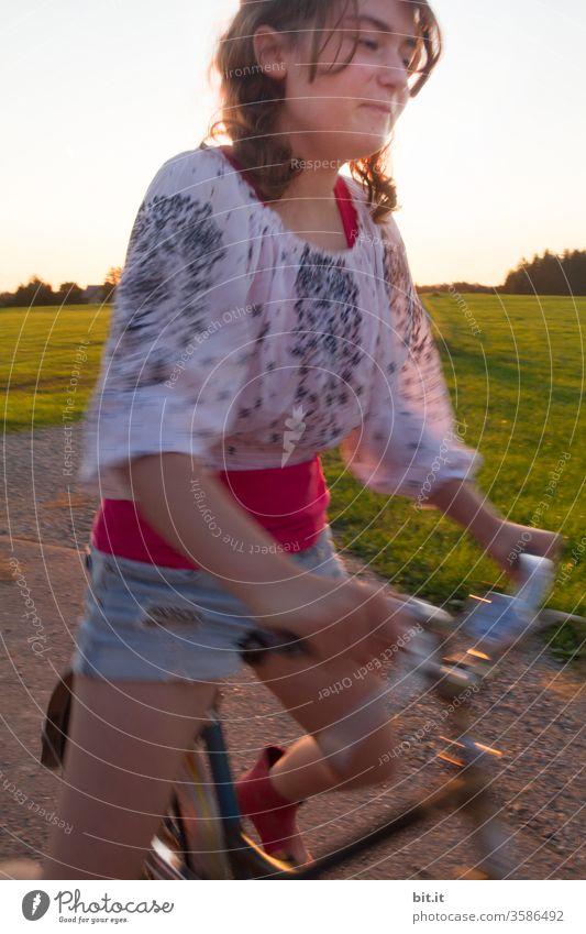 Schmunzelnd tritt die brünette Jugendliche, in modischer Bluse und Shorts in die Pedale, dabei grinst sie frech. Sommerliche, schnelle, dynamische Fahrradtour auf der Straße, vorbei an grünem Gras einer Wiese und Bäumen, mit Unschärfe durch die Bewegung.