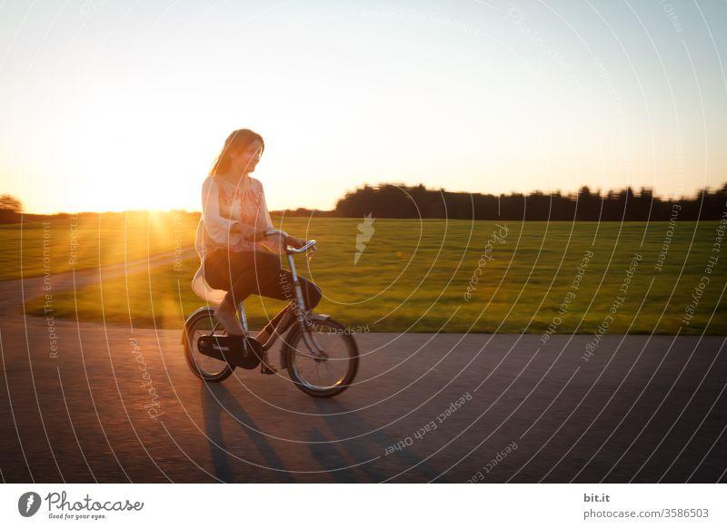Langhaarige, brünette Jugendliche, fährt bei Abendlicht mit einem kleinen Fahrrad auf der Straße. Fahrradtour in der Dämmerung, vorbei an grüner Wiese und Wald, wobei der Teenager, wie ein lustiger Riese auf dem überdimensional, winzigen Zwergen-Rad wirkt.