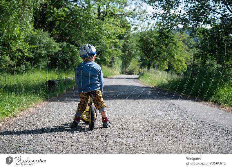 Kind mit Fahrrad auf einem Weg Wege & Pfade Laufrad wachsen Kindheit lernen Verkehr Außenaufnahme Fahrradfahren Tag Straße Farbfoto Verkehrswege Mobilität