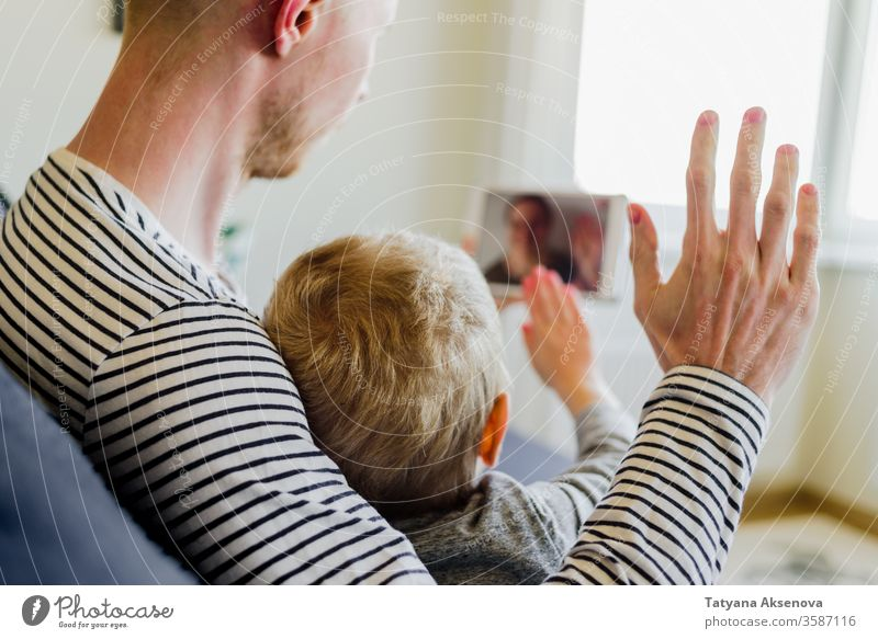 Vater und Sohn führen Videoanruf bei der Mutter Anruf Familie Internet Technik & Technologie modern Menschen heimwärts Talkrunde Computer Mitteilung Frau jung