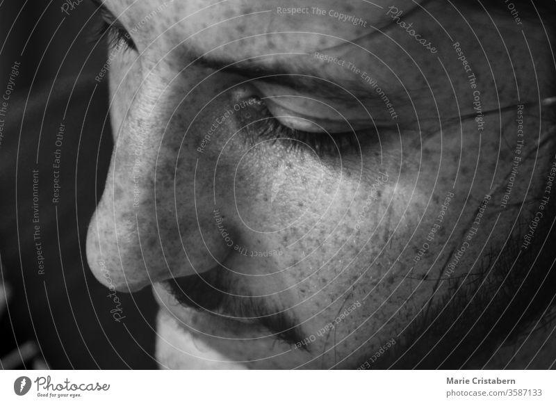 Nahaufnahme eines Mannes mit nüchternem Gesichtsausdruck, um das Konzept der männlichen Verwundbarkeit, Intimität, Geschlechtsidentität, Verschwiegenheit und psychischen Gesundheit zu zeigen