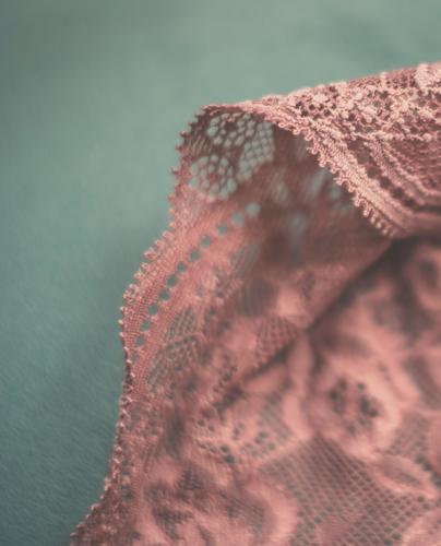 Rosa Spitze vor blauem Hintergrund rosa Stoff Bekleidung feminin geblümt floral Detail zart sexy sinnlich Unterwäsche Erotik Höschen Slip