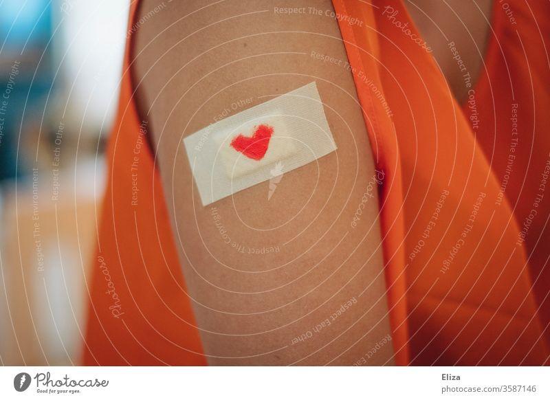 Ein Pflaster mit einem kleinen roten Herzen darauf auf dem Oberarm einer Frau. Konzept Impfung und Fürsorge. Verletzung trösten haut Liebe Schmerz Gefühle Wunde