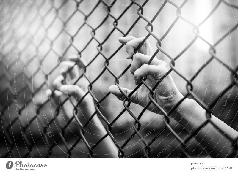 Depressionen, Ärger und Leben zählen. Schwarz-Weiß-Filter, Frauen Hand am Maschendrahtzaun. mit Stacheln versehen Barrikade Barriere schwarz Borte Mobbing