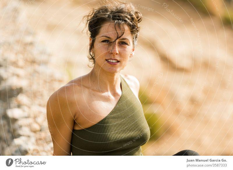 Eine selektive Scharfstellung einer schönen Latina, die auf dem Felsen sitzt Frau Mädchen hübsch Schönheit jung weiß schwarz Erwachsener Porträt attraktiv