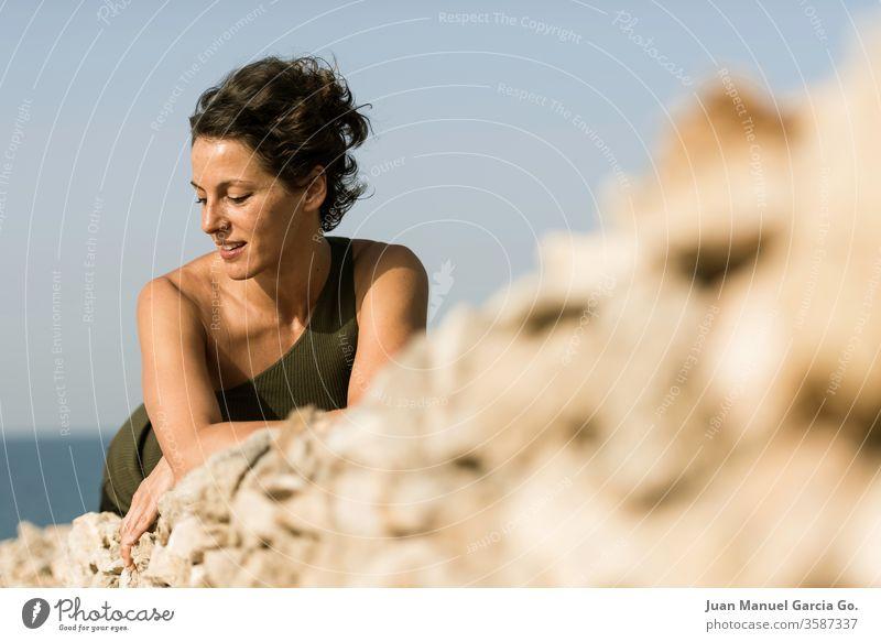 Selektive Scharfstellung einer schönen weiblichen Latina, die auf einem Felsen liegt Frau Mädchen hübsch Schönheit jung weiß schwarz Erwachsener Porträt