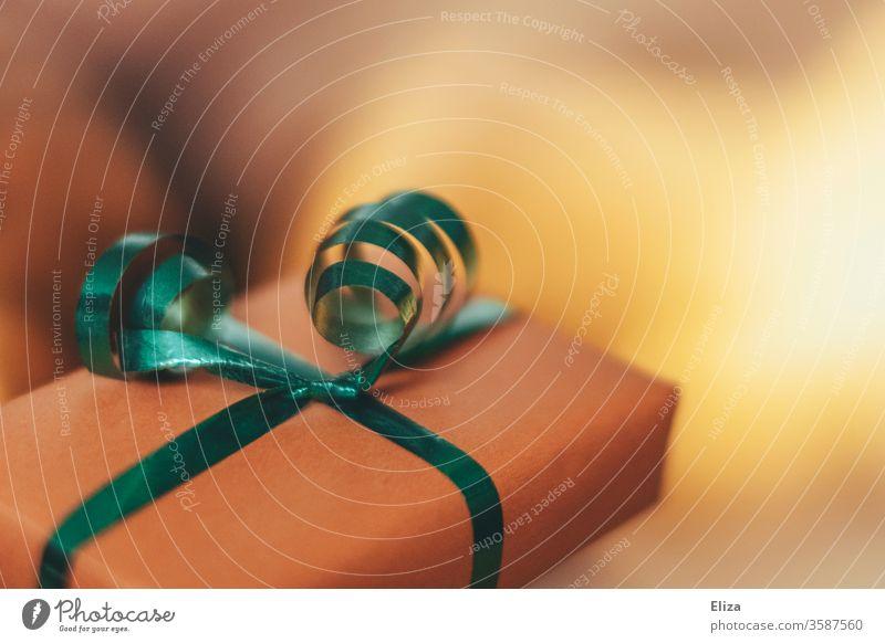 Ein verpacktes Geschenk mit Geschenkband vor einem unscharfen Hintergrund Weihnachtsgeschenk hübsch Geschenkpapier rosa Detail schenken Geburtstag Verpackung