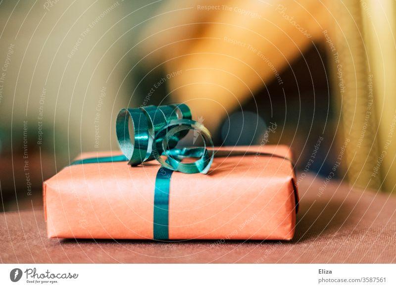 Ein Geschenk mit Geschenkband zu Weihnachten oder zum Geburtstag vor unscharfem Hintergrund. schenken Muttertag verpackt Weihnachten & Advent Feste & Feiern