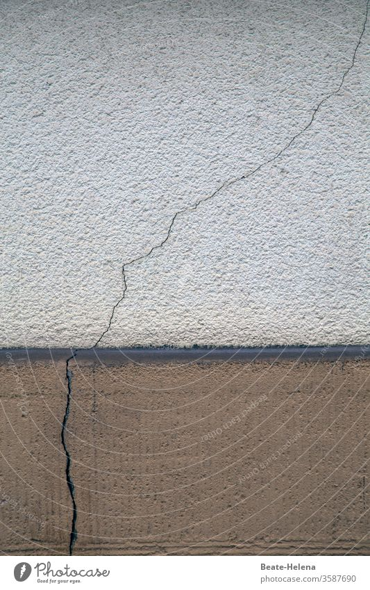 Rissgenau: durchgehender Riss im Mauerwerk Wand Farbfoto Architektur Sockel Beton schadhaft wackelig kaputt Einsturzgefahr instabil Menschenleer