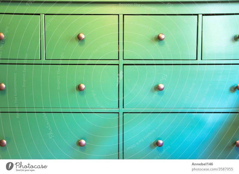 Grüner Schrank mit verschiedenen Schubladen, farbenfroher Holzschrank Nahaufnahme Retro-Design Hintergrundtextur Blume medizinisch Frau Business Mode Grunge