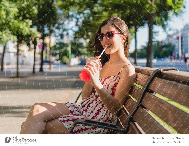 Süße Frau auf der Straße. Sie trinkt im Sommer einen kalten Tee. Sie trägt eine Sonnenbrille. im Freien Mädchen Menschen jung trinken Wellness aktiv blau