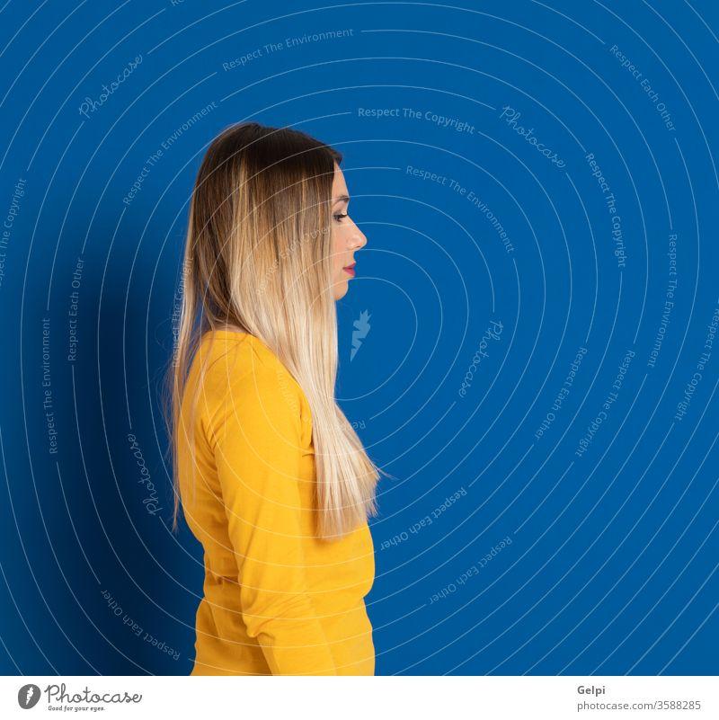 Blondes Mädchen mit gelbem T-Shirt Person blau blond Profil Seite Nase Fairness Behaarung Kopf Ausdruck gestikulieren jung schön Frau Mode Atelier Kaukasier