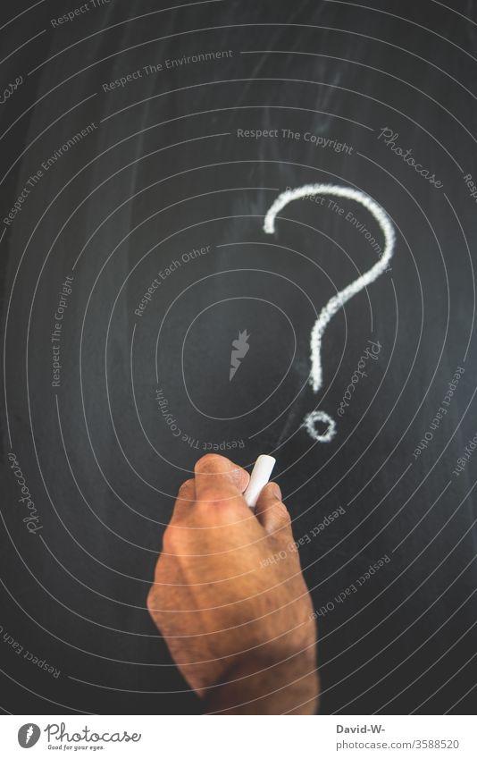 mit Kreide ein Fragezeichen an die Tafel malen Fragen fragend unwissen unsicher Lösung Wieso warum weshalb? fragen über fragen Farbfoto Schriftzeichen Zeichen