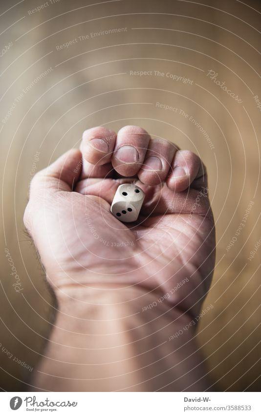 einen Würfel in der Hand halten Mann festhalten würfeln Glückspiel glück pecht wünschen sucht suchtgefahr glückspilz Pechvogel Spielen Spieler Glücksspiel