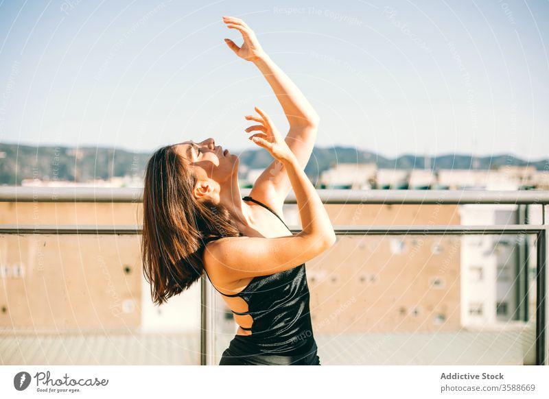 Gelassene Frau tanzt auf der Terrasse Tanzen Anmut Tänzer Gelassenheit ausführen Sommer ruhig beweglich Handfläche Baum urban jung aufschauend Windstille