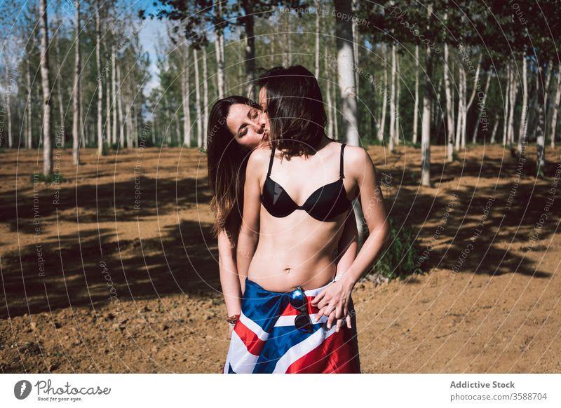 Junges Frauenpaar küsst sich im Park Paar lesbisch Kuss Sommerzeit Umarmung jung Unterwäsche Liebhaber Dessous BH anhaben Großbritannien England schwul Fahne