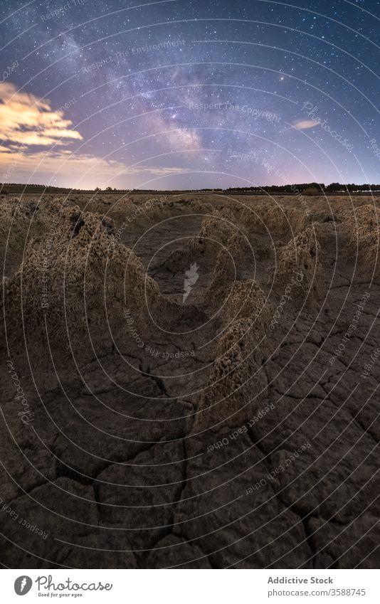 Anonyme Person steht in sternenklarer Nacht auf felsigem Terrain Mann Felsen Gelände Milchstrasse Fackel Silhouette Landschaft vulkanisch porig malerisch Himmel