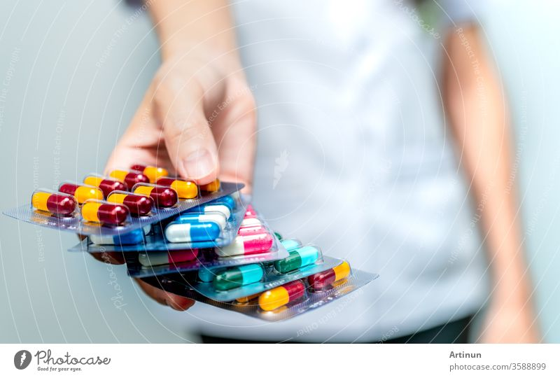 Apotheker oder Arzt hält eine Packung antibiotischer Kapseltabletten in der Hand und gibt sie dem Patienten oder den Menschen. Übermäßiger Gebrauch von Antibiotika. Resistenz gegen antimikrobielle Arzneimittel. Gemeindeapotheker. Drugstore-Hintergrund.