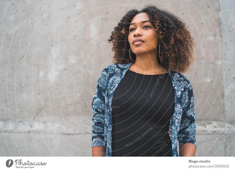 Afroamerikanische Frau gegen graue Wand. Afro-Look jung Mädchen Gesicht Ausdruck Erwachsener Blick Mode schwarz Stehen Lächeln selbstbewusst Behaarung brünett