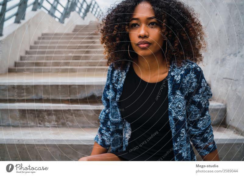 Afroamerikanische Frau, die auf Stufen sitzt. Afro-Look grau jung Mädchen Gesicht Wand Ausdruck Erwachsener Blick Mode schwarz Stehen Lächeln selbstbewusst