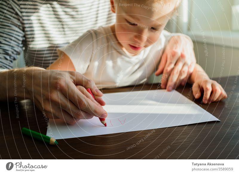 Vater lehrt Kind schreiben oder zeichnen Bildung heimwärts Lehre Homeschooling Schule schreibend Lernen Hausaufgabe Lehrer Menschen Sitzen Eltern Familie