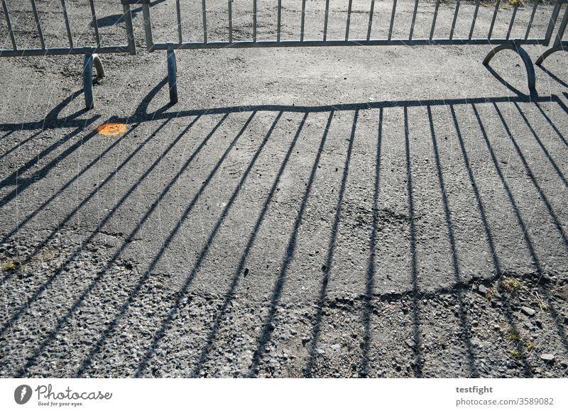 Absperrgitter absperrung Zaun mobil Trennung Schatten Schattenwurf Sonnenlicht Boden Teer Asphalt marode Gegenlicht