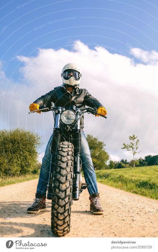 Mann mit Helm auf einem Custom-Motorrad Blick von unten Biker benutzerdefiniert altehrwürdig Rad Fahrrad retro Reiter Fahrzeug Verkehr posierend jung
