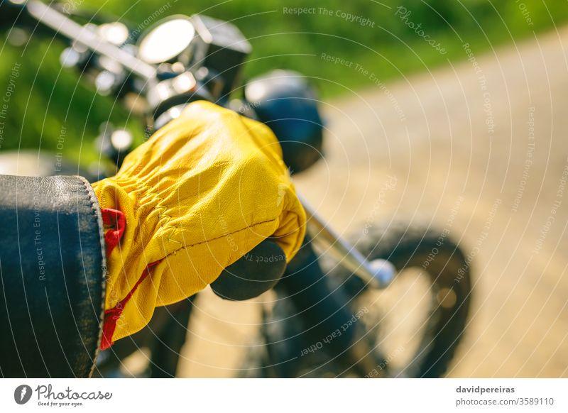 Bikerhand mit Handschuhen, die den Lenker greifen. gelb Detailaufnahme Motorrad altehrwürdig Mann benutzerdefiniert Fahrrad retro Reiter Fahrzeug Verkehr jung
