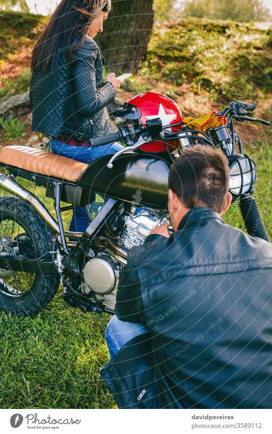 Mann repariert sein Motorrad, während seine Freundin das Handy betrachtet Fixierung reparierend Panne benutzerdefiniert Beschädigte Frau Blick Mobile Reiter