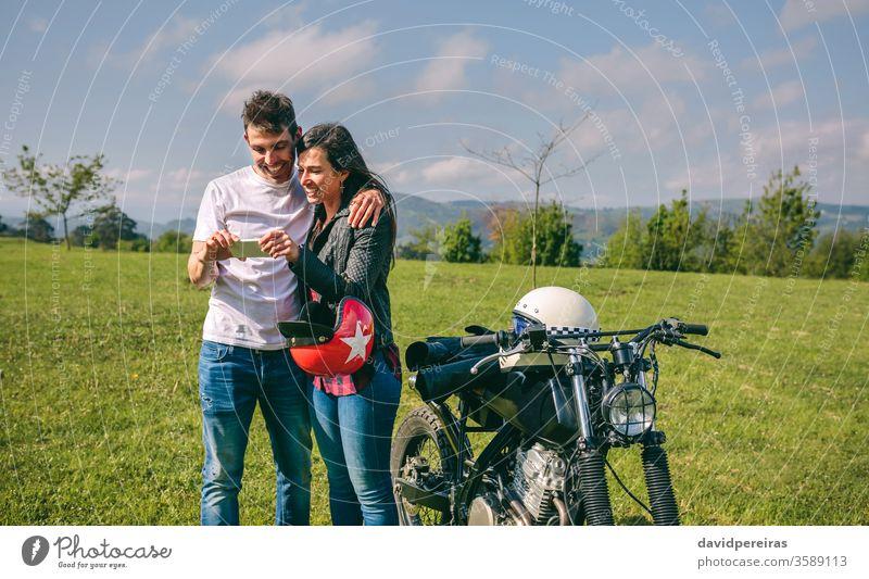 Paar, das mit einem Motorrad mobil aussieht Glück Blick Smartphone Bild Video Ausflug Mann Lächeln Handy umarmend Motorradhelm benutzerdefiniert attraktiv