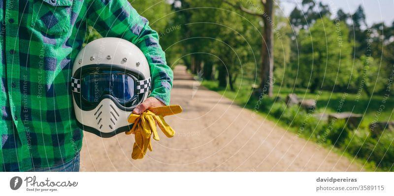 Mann posiert mit Motorradhelm und Handschuhen unkenntlich kariertes Hemd Straße Transparente Netz panoramisch Panorama altehrwürdig cool retro Reiter Biker Mode