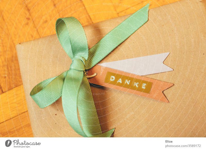Ein Geschenk mit einer Schleife und einem Anhänger auf dem das Wort Danke geschrieben steht. Dankbarkeit. verpackt bedanken eingepackt Buchstaben Freude