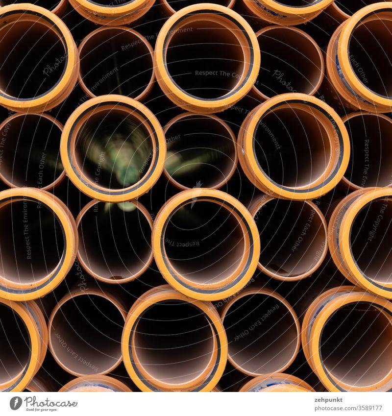 Viele orangene Röhren gesehen von der Stirnseite. In dreien schimmert das Grün des Hintergrunds hervor. viele Baustelle Stapel schwarz grün Kreise Muster