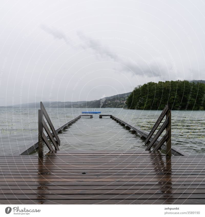 Nasse Holzbretter eines Badestegs, ein Holzgeländer in den See, eine Absperrung im See, eine blaue Badeinsel, alles bei regnerisch grauem Wetter Badeanstalt