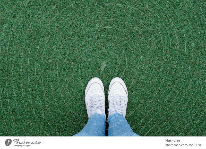 Selfie der Füße in weißen Turnschuhen auf grünem Grashintergrund mit Kopierraum, Frühling und Sommer mit modischem Lifestyle-Konzept im Freien Abenteuer Foto
