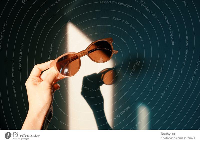 Frauenhand hält modische Sonnenbrille mit Sonnenlichtschatten mit Schatten an der Wand, Trend- und Sommerkonzept Brille stylisch Schutz Linse optisch Feiertag