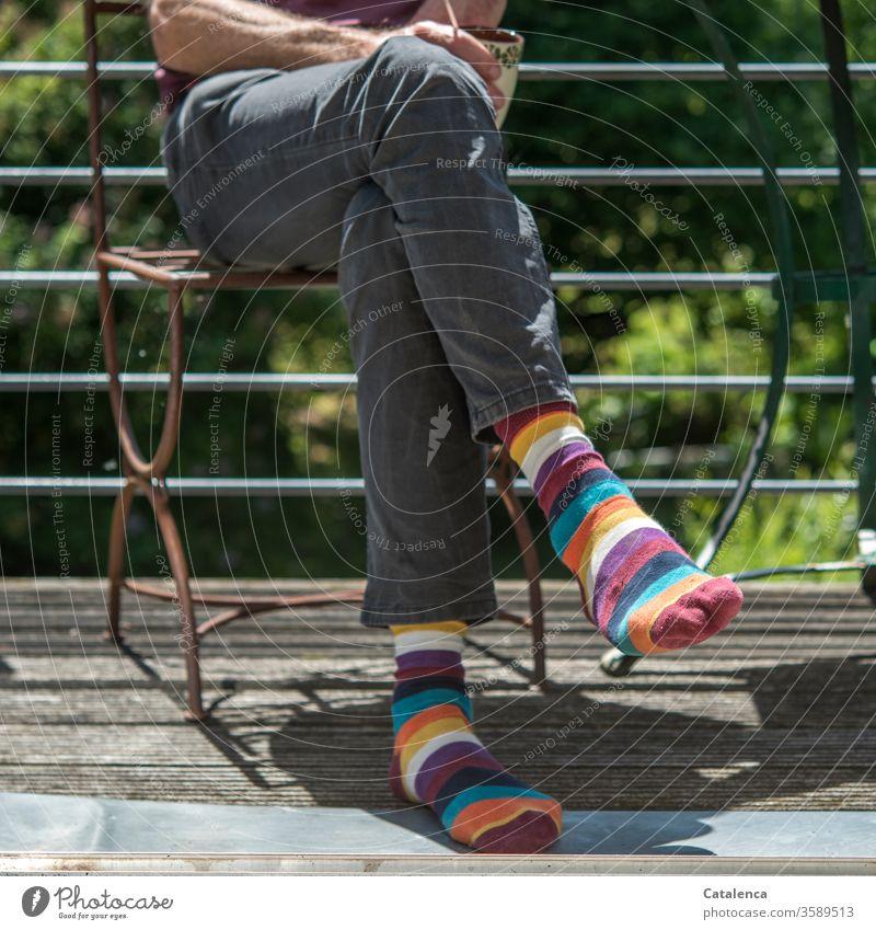 Haute Couture |  abgehobenes Modebewusstsein; knallige Ringelsocken Mann Beine Füsse Bekleidung Trend Fuß Strümpfe Mensch sitzend Stuhl Balkon Sommer bunt