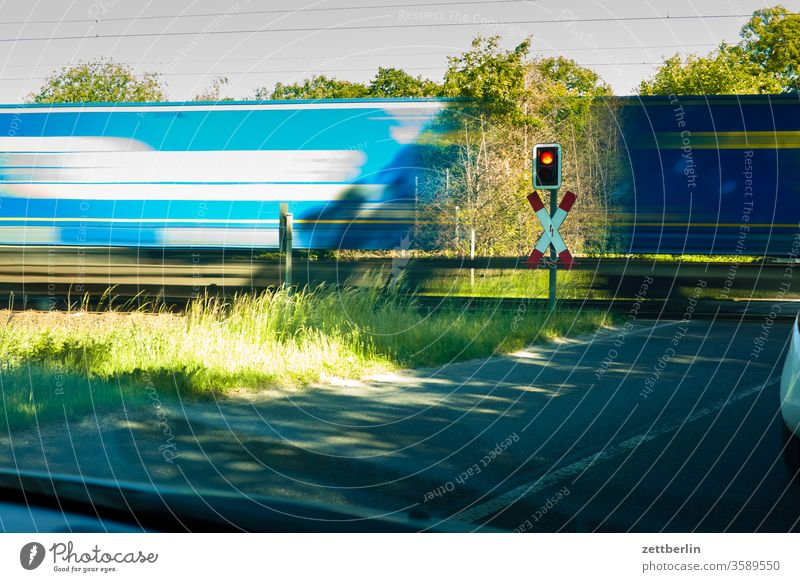 Güterzug am Bahnübergang bahn bahnübergang durchfahrt eisenbahn güterzug logistik lok lokomotive schnell schnelligkeit transport versorgung waggon eile hektik