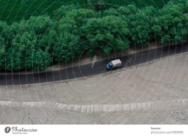 Eine Luftaufnahme eines fahrenden Lastwagens auf einer leeren Straße, die durch grüne Bäume und die Wiesen getrennt ist. Transport PKW Lkw-Transport reisen