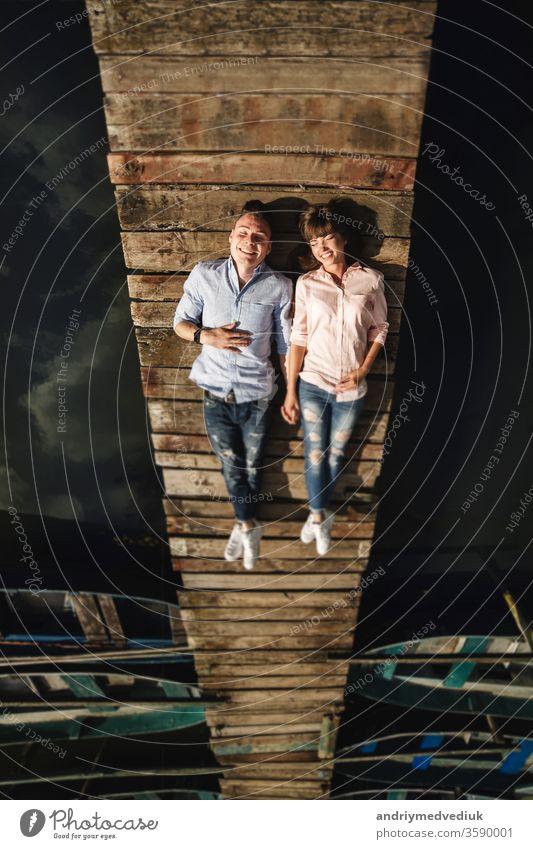 Perfektes Date. Schönes junges Paar und lächelnd auf dem Pier liegend. glücklicher junger Mann und Frau lachend auf dem hölzernen Pier am Wasser liegend