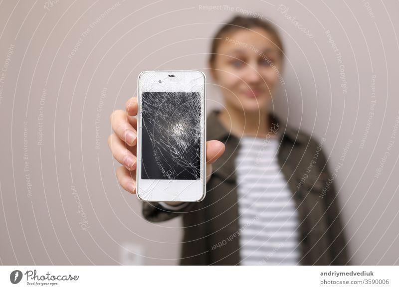 Frustrierte junge Frau hält Handy mit zerbrochenem Bildschirmglas in der Hand. Das Display des Telefons muss repariert werden. Isoliert auf grauem Hintergrund. selektiver Fokus auf Smartphone