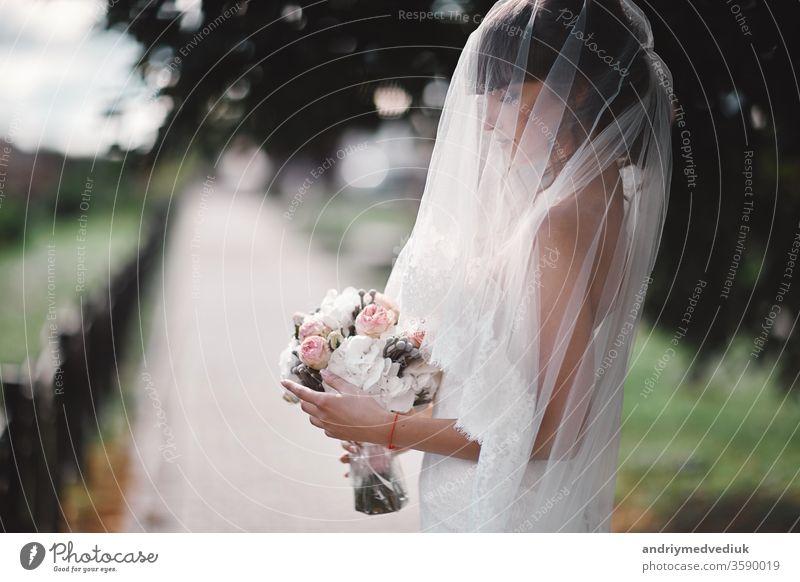 Schöne junge Braut in einem weißen Luxuskleid und in einem Brautschleier mit einem Blumenstrauß, der im Freien posiert. hochzeitsporträt. kopierraum Hochzeit