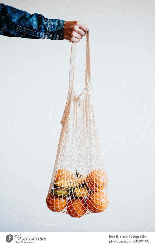 frau han hält moderne einkaufstasche aus weissem textil mit orangen. vorderansicht, weisser hintergrund. zero waste concept Baumwolltasche keine Verschwendung
