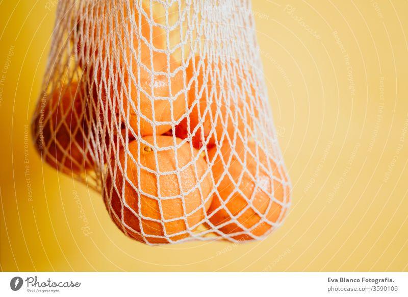 Null-Abfall-Konzept. Moderne Einkaufstasche aus weißem Textil mit Orangen. Vorderansicht, gelber Hintergrund. Nahaufnahme orange Baumwolltasche