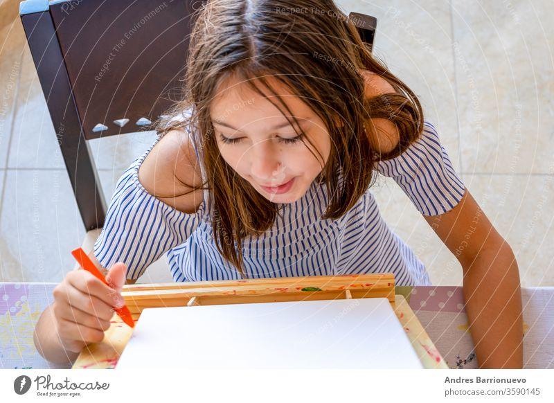 Hübsches kleines Mädchen in einem weiß-blau gestreiften Kleid, das auf einer Staffelei malt Spaß Fröhlichkeit Bildung wenig Glück pulsierend Farbe lernen