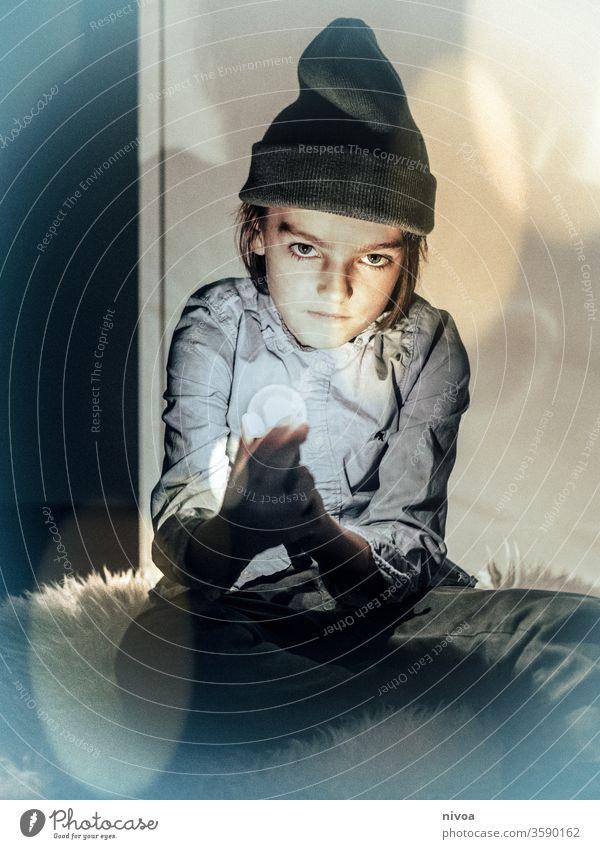 Junge mit Glühbirne in der Hand Kind Mensch Gesicht Porträt Blick Mund Freude Kinder Auge Zauberei u. Magie Zauberer Farbfoto Kindheit Kopf Beanie Schafswolle
